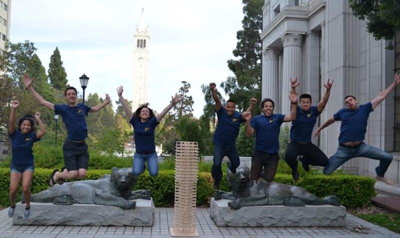 Seismic student team jumping in front of bear statue on Berkeley campus with wooden building model in front of them